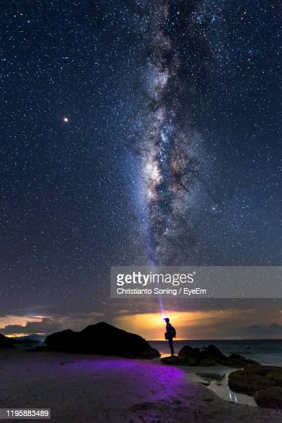 silhouette person standing on beach against sky at night - canterbury region new zealand stock pictures, royalty-free photos & images