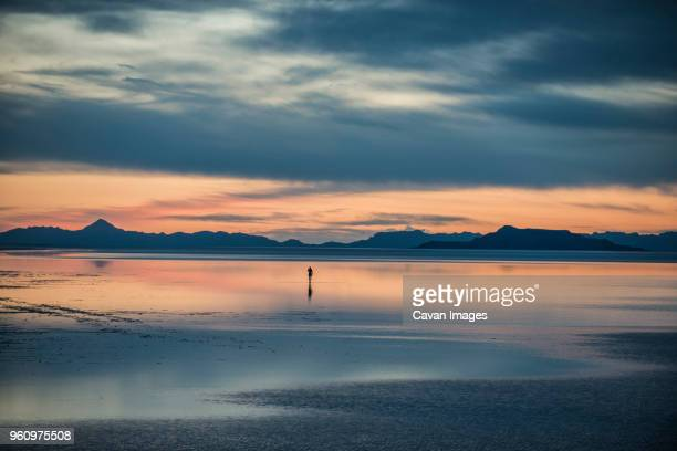 silhouette person standing on bonneville salt flats against cloudy sky - bonneville salt flats stock pictures, royalty-free photos & images