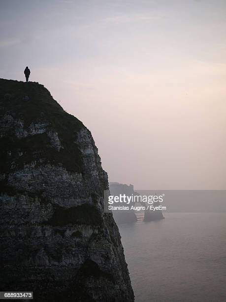 Silhouette Person Standing On Cliff At Etretat Against Sky