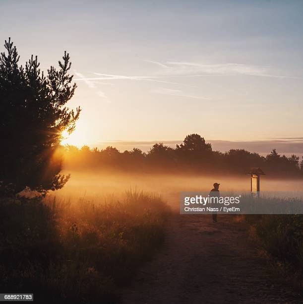 Silhouette Person Standing On Dirt Road Amidst Fog During Sunrise