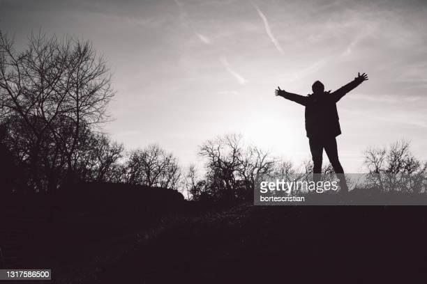 silhouette person standing on field against sky during sunset - bortes stockfoto's en -beelden