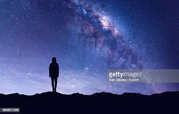 silhouette person standing on field against star field - constellation stock pictures, royalty-free photos & images