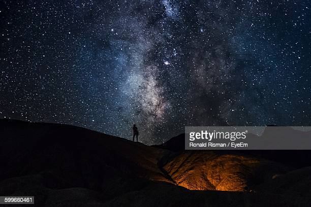 silhouette person standing on landscape against star field at night - aiming stock pictures, royalty-free photos & images