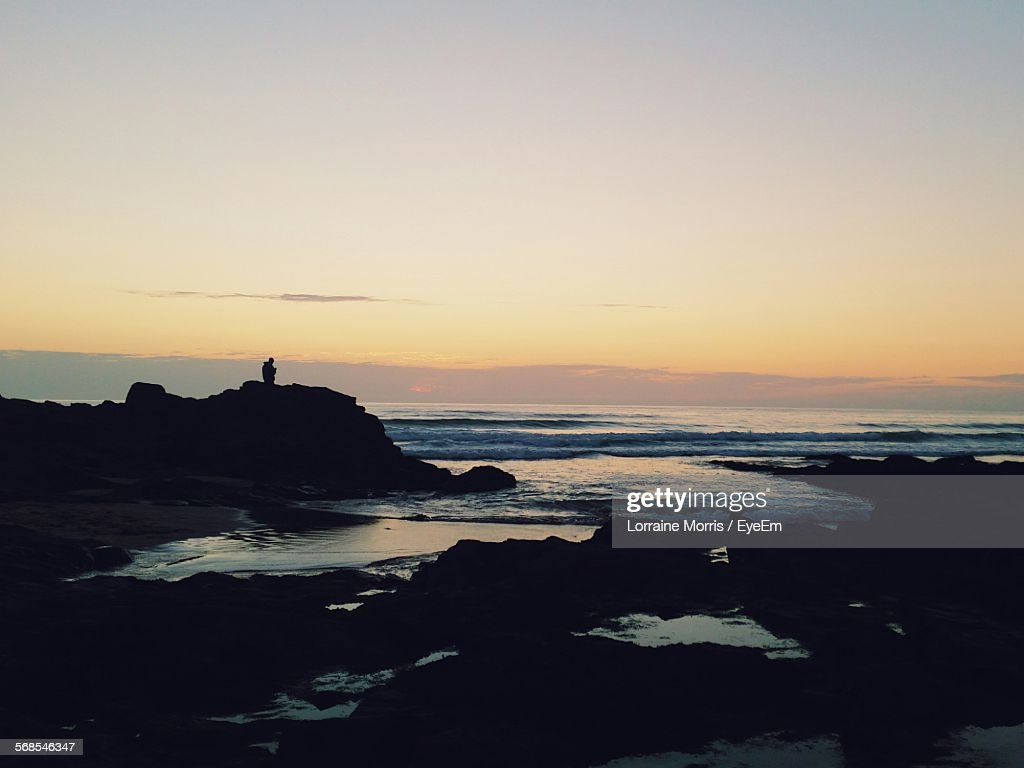 Silhouette Person Standing On Rock Against Sunset Sky In Cornwall : Stock Photo