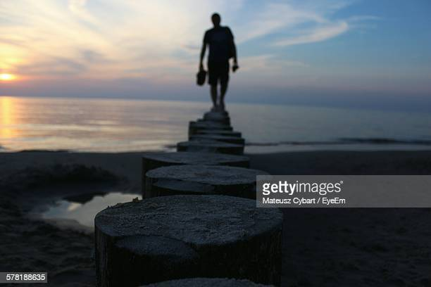 Silhouette Person Standing On Wooden Post At Beach During Sunset