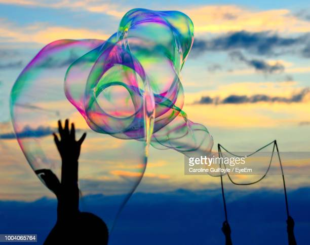 Silhouette Person Touching Bubbles Against Sky During Sunset