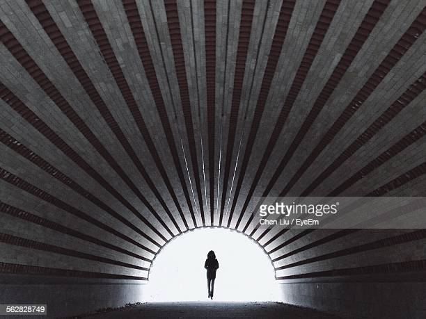 Silhouette Person Walking In Tunnel