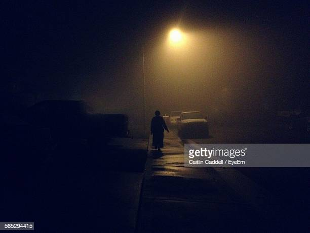 Silhouette Person Walking On Footpath Under Street Light At Night