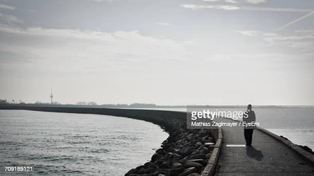 Silhouette Person Walking On Pier In Sea Against During Sunny Day