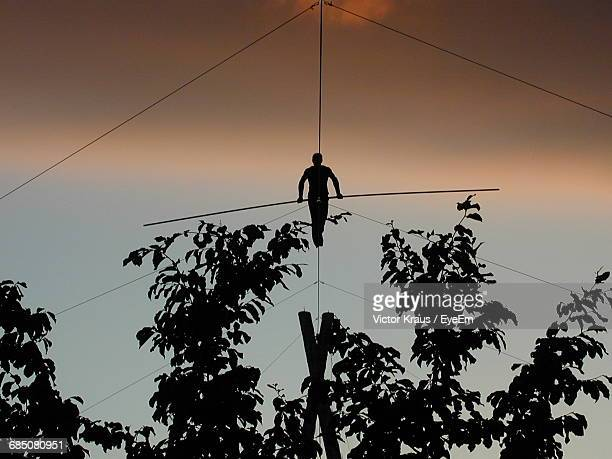 Silhouette Person Walking On Rope Against Sky During Sunset