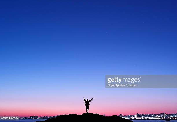 silhouette person with arms raised on hill against clear blue sky - 澄んだ空 ストックフォトと画像