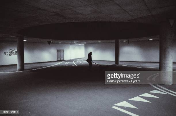 Silhouette Person With Dog Standing Under Parking Garage