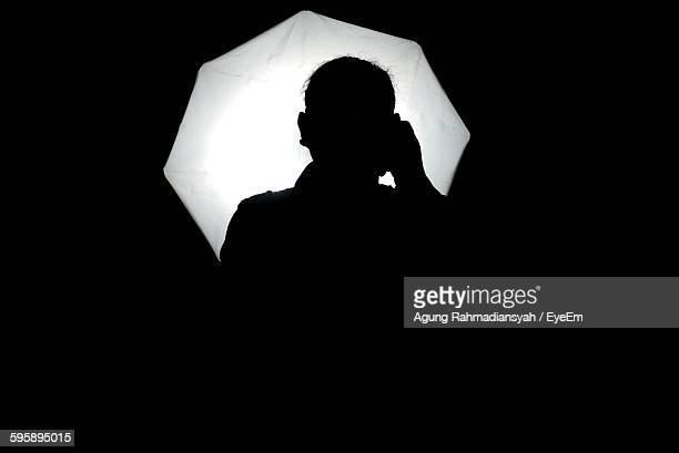 silhouette person with illuminated umbrella in studio - photo shoot photos et images de collection