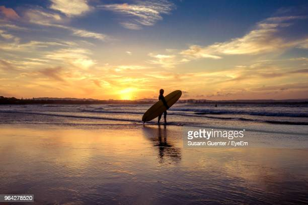 Silhouette Person With Surfboard Walking In Sea Against Sky During Sunset