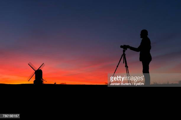Silhouette Photographer With Tripod By Windmill Against Sky At Dusk