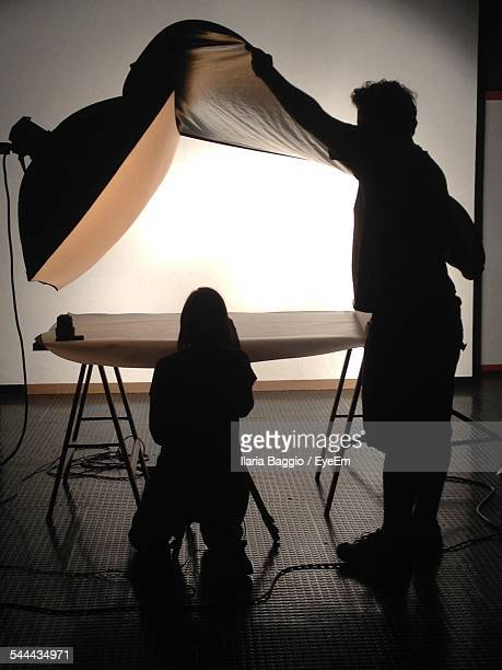 silhouette photographers preparing for the photo shoot in studio - film or television studio stock pictures, royalty-free photos & images