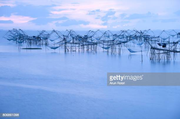 Silhouette picture reflection of Square dip fishing traps in the lake, Pakpra, Phatthalung, Thailand.