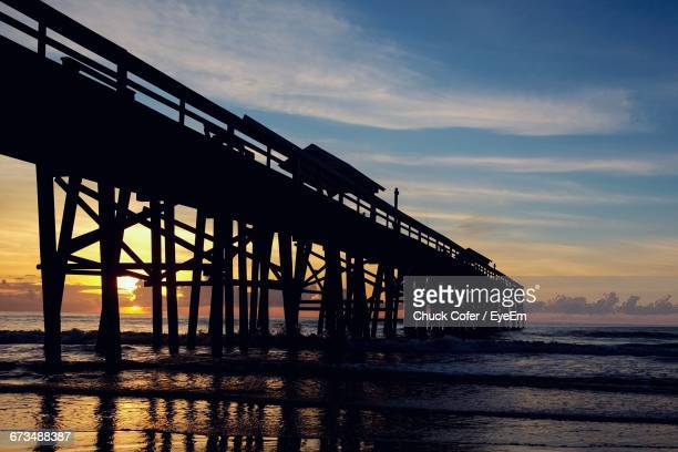 Silhouette Pier At Amelia Island Against Cloudy Sky During Sunset