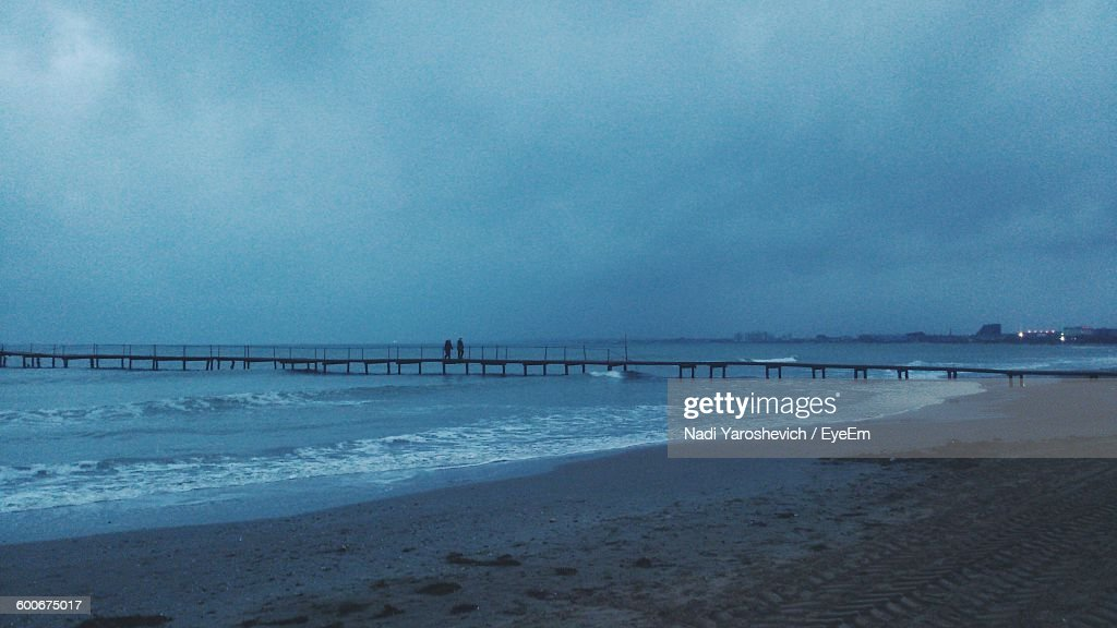 Silhouette Pier At Beach Against Cloudy Sky At Dusk : Stock Photo