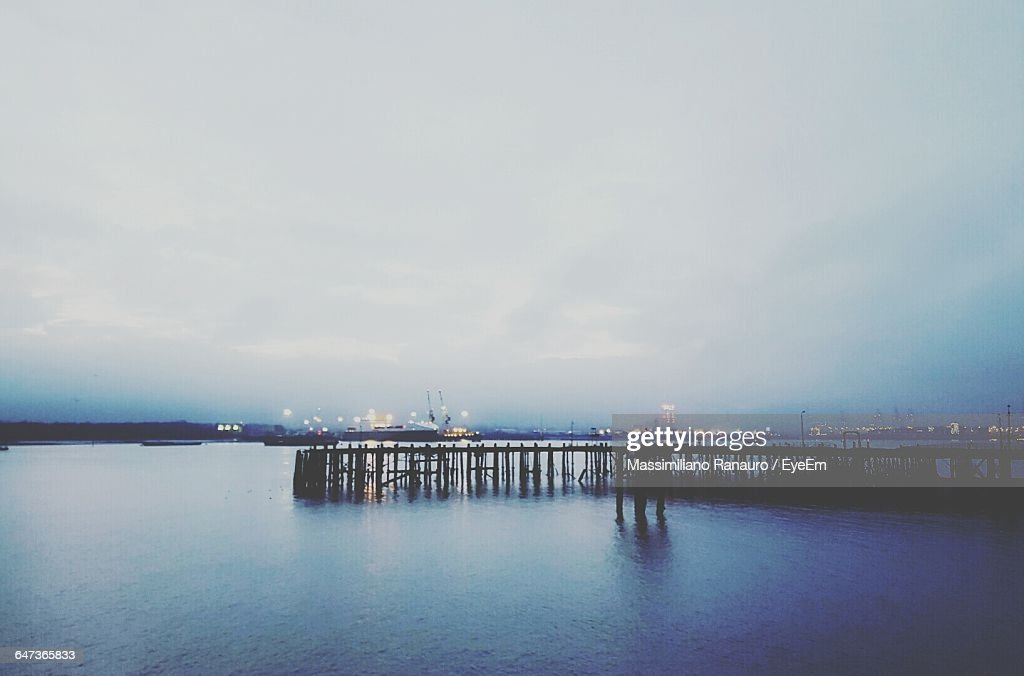 Silhouette Pier By River Against Cloudy Sky At Dusk : Stock Photo