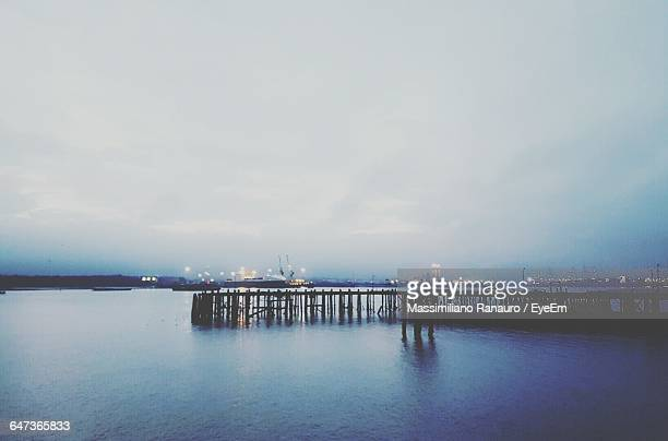 silhouette pier by river against cloudy sky at dusk - massimiliano ranauro stock pictures, royalty-free photos & images