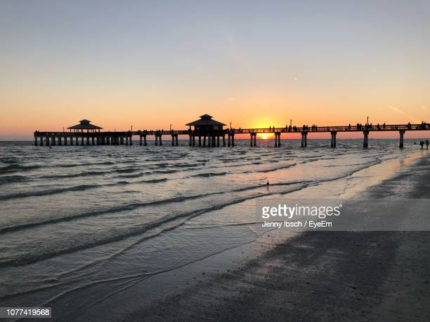 silhouette pier on beach against clear sky during sunset - fort myers stock pictures, royalty-free photos & images