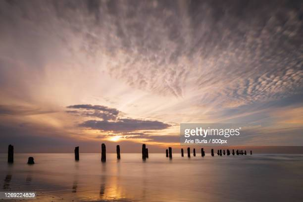 silhouette pier on sea against sky during sunset, netanya, israel - netanya stock pictures, royalty-free photos & images