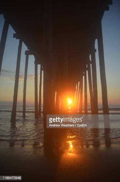 silhouette pier on sea against sky during sunset - kitty hawk beach stock pictures, royalty-free photos & images