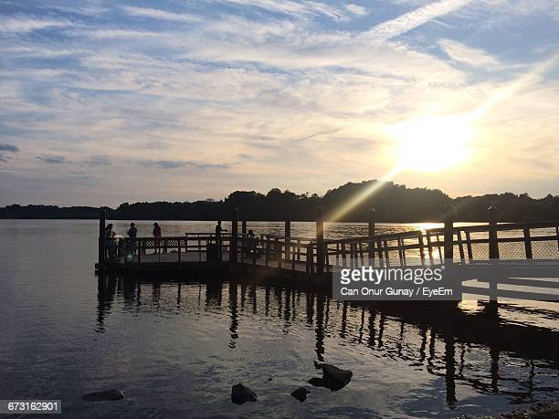 silhouette pier over lake at black hills regional park during sunset - black hills stock photos and pictures