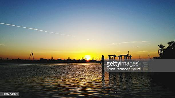 Silhouette Pier Over River Against Sky During Sunset