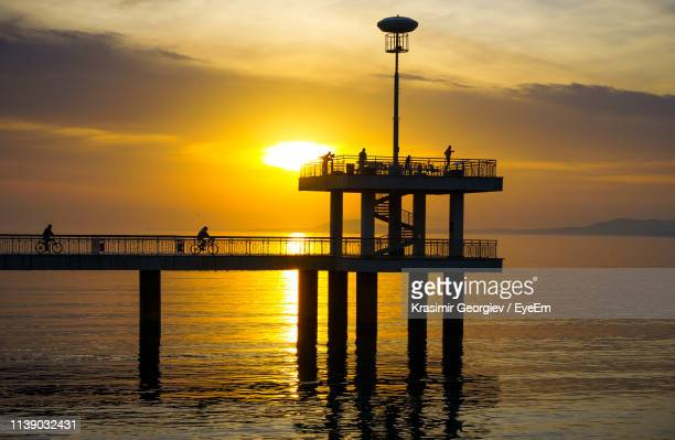 silhouette pier over sea against sky during sunset - krasimir georgiev stock photos and pictures