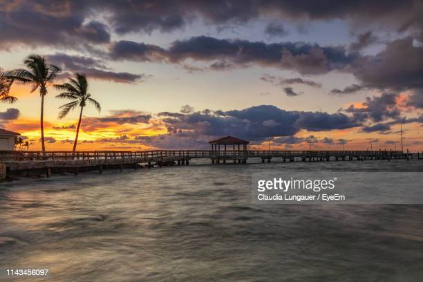 silhouette pier over sea against sky during sunset - key west stock pictures, royalty-free photos & images