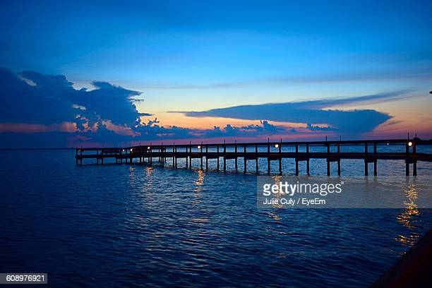 silhouette pier over sea against sky during sunset - julie culy stock pictures, royalty-free photos & images