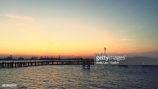 silhouette pier over sea against sky during sunset - southampton england stock pictures, royalty-free photos & images
