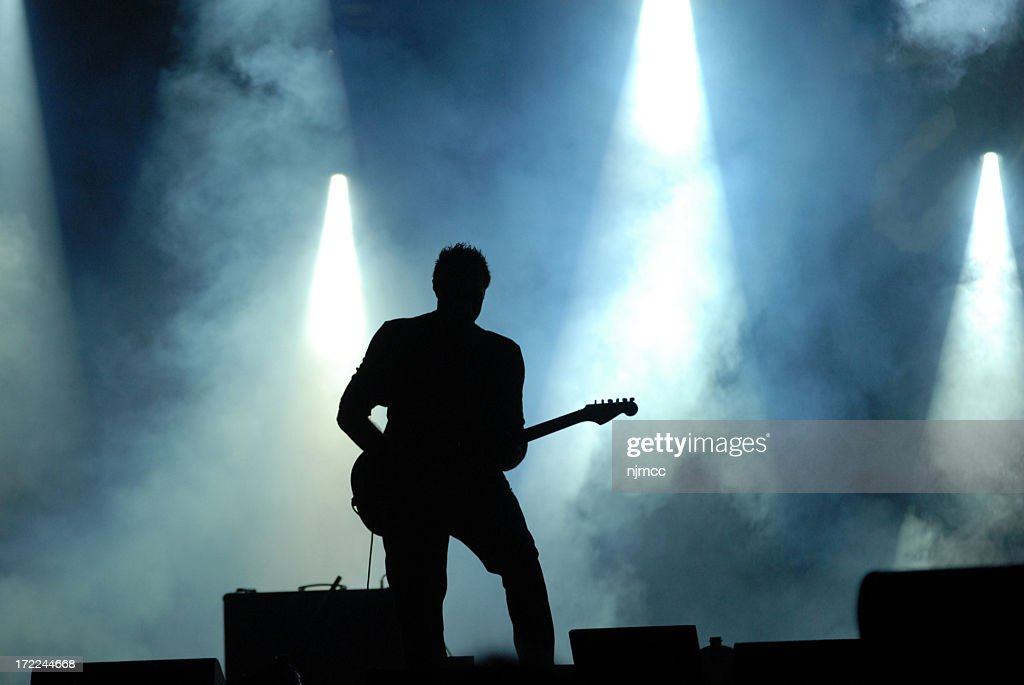 A Silhouette Playing A Guitar At A Concert Stock Photo ...