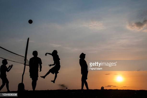 Silhouette playing volleyball at beach