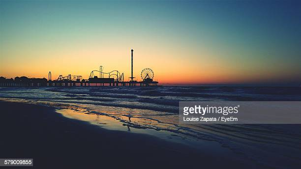 silhouette pleasure pier against clear sky at sunset - galveston stock pictures, royalty-free photos & images