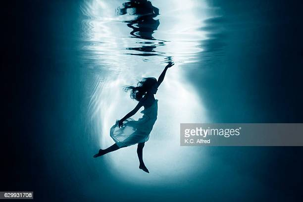 Silhouette portrait of a female model underwater appearing to dance in a swimming pool in San Diego, California.