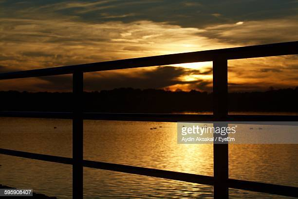 Silhouette Railing Against River During Sunset