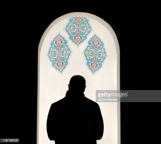 silhouette rear view of imam praying in mosque - イマーム寺院 ストックフォトと画像