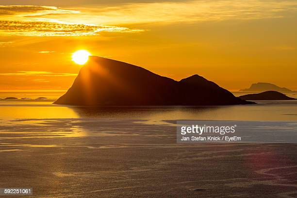 Silhouette Rock Formation At Beach Against Orange Sky