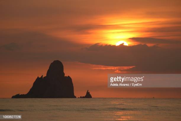 Silhouette Rock Formation In Sea Against Orange Sky