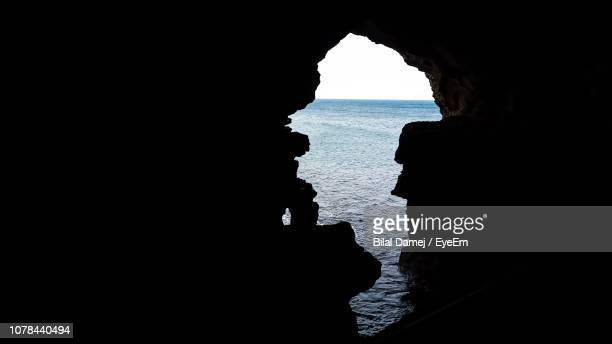 silhouette rock formation in sea against sky - geology stock photos and pictures