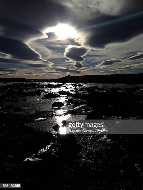 silhouette rocks in waterfall against cloudy sky at sunset - selfoss stock photos and pictures