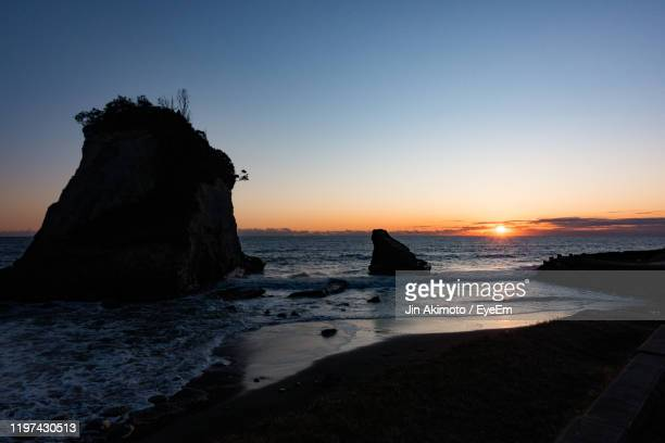 silhouette rocks on beach against sky during sunset - 千葉市 ストックフォトと画像