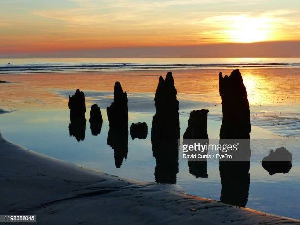 silhouette rocks on beach against sky during sunset - west sussex stock pictures, royalty-free photos & images