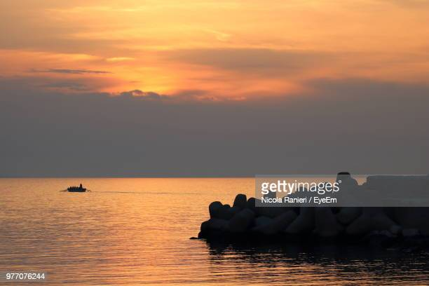 Silhouette Rocks On Sea Against Sky During Sunset