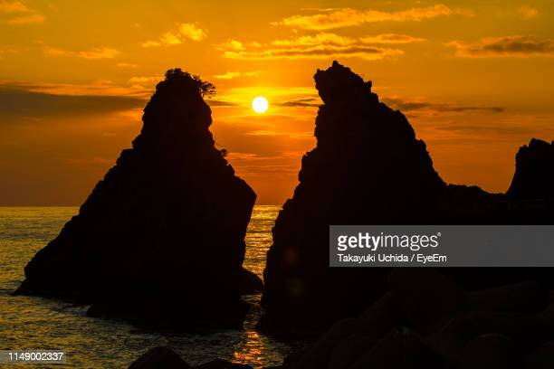 silhouette rocks on shore against sky during sunset - fukui prefecture - fotografias e filmes do acervo