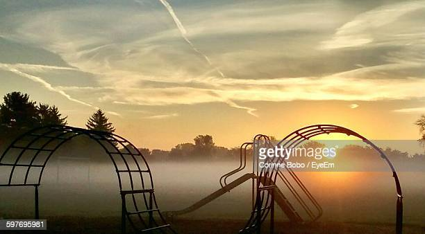 silhouette rollercoaster at playground against sky during sunrise - corinne paradis photos et images de collection