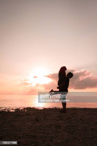 Silhouette Romantic Couple Standing At Beach Against Sky During Sunset